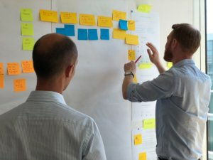Two people construct their product marketing plan on sticky notes